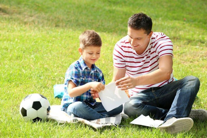 做纸飞机的小男孩和他的父亲户外 免版税库存图片