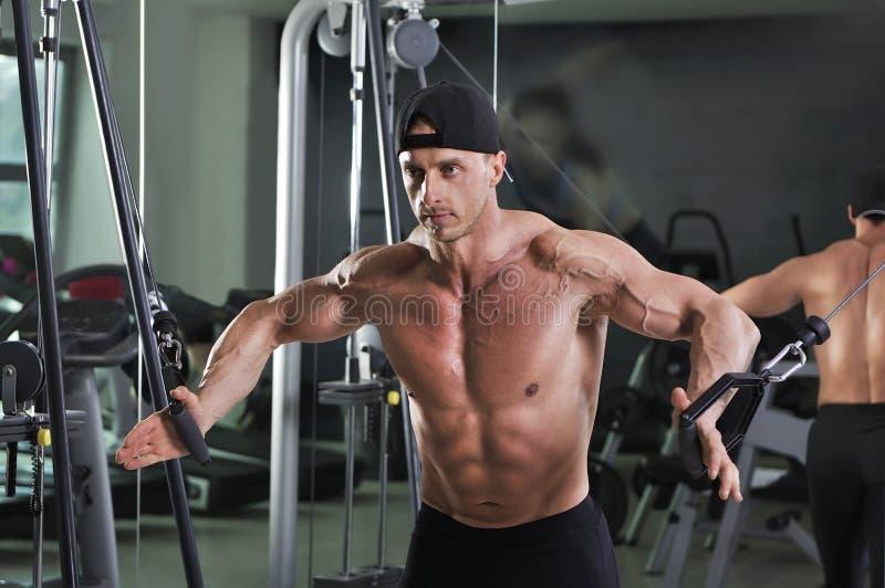做缆绳天桥锻炼的英俊的强有力的运动人 库存图片