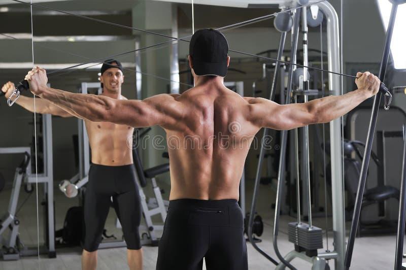 做缆绳天桥锻炼的英俊的强有力的运动人 免版税库存照片
