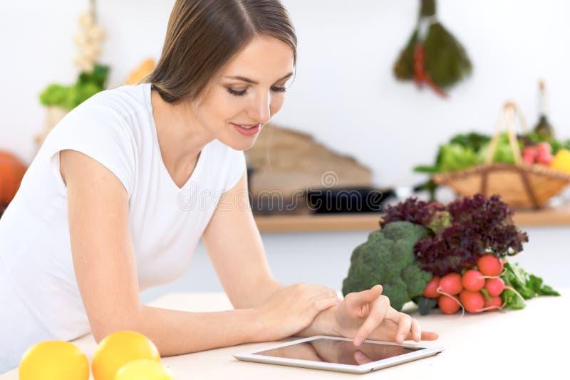 做网上购物的厨房的少妇由片剂计算机和信用卡 库存照片