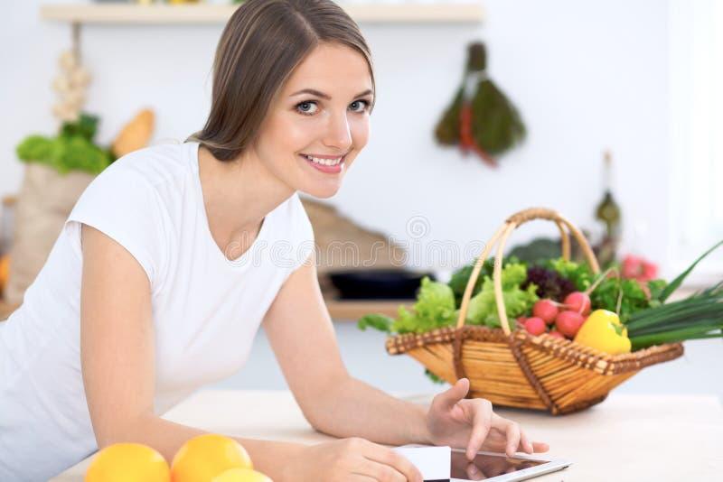 做网上购物的厨房的少妇由片剂计算机和信用卡 库存图片