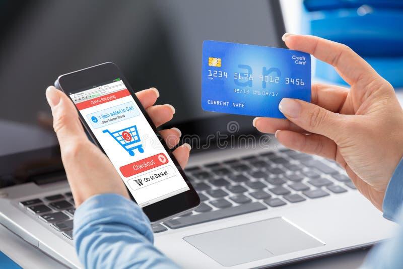 做网上购物的妇女使用信用卡 库存图片