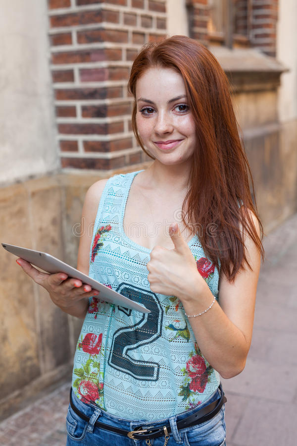 做网上购物的年轻俏丽的女孩使用片剂 都市bac 图库摄影