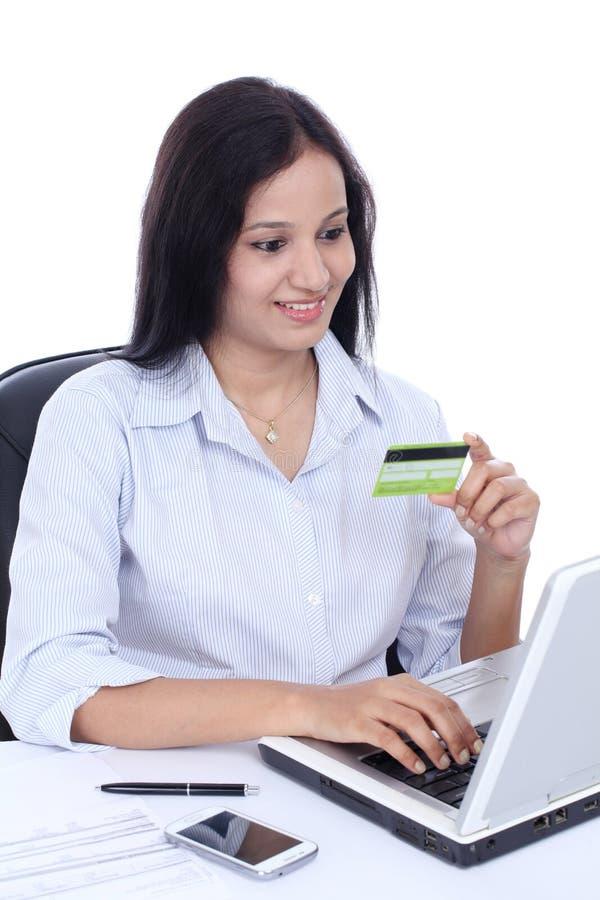 做网上购物的愉快的年轻女商人 库存图片