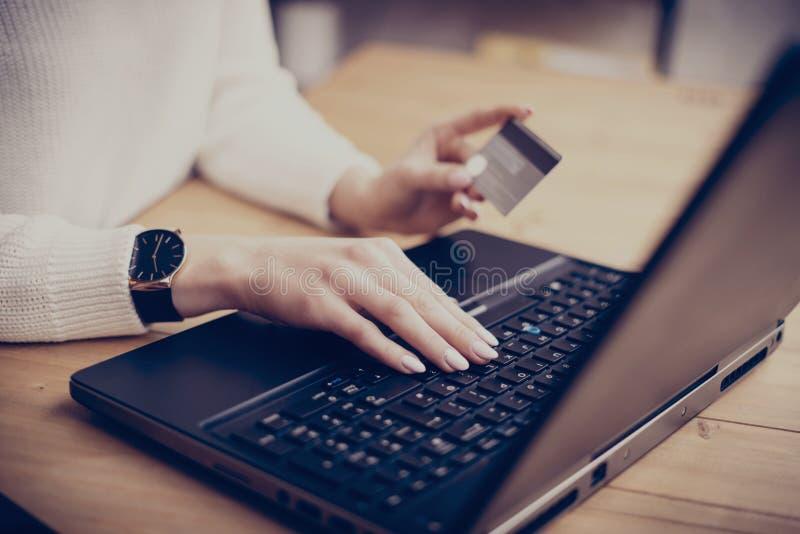 做网上购物通过膝上型计算机,键入在键盘和使用她的信用卡的年轻女实业家 水平,影片 库存图片