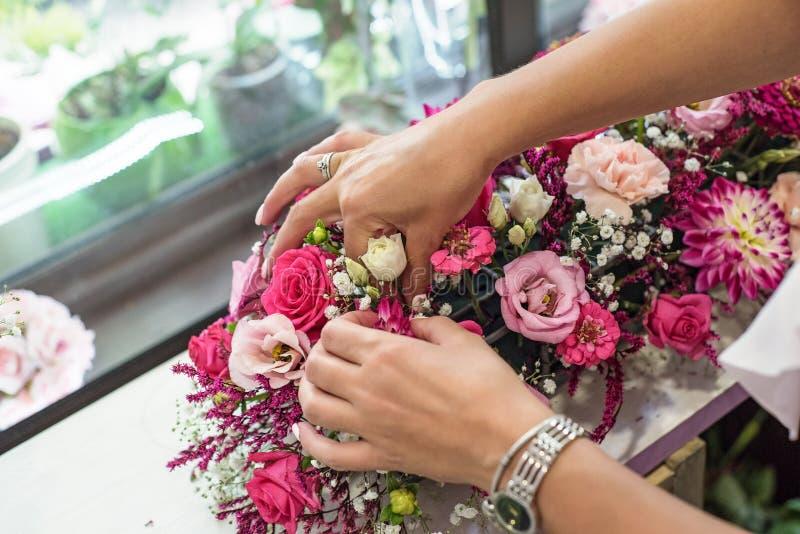 做美丽的花束的女性卖花人在花店 库存照片