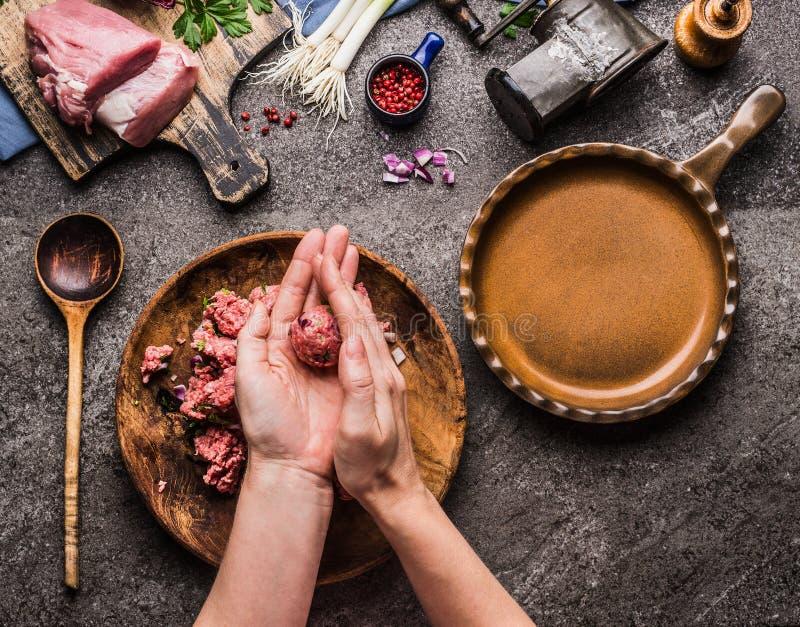 做肉丸的女性手在厨房用桌背景用肉、力量肉、绞肉机和匙子,顶视图 烹调, reci 免版税图库摄影