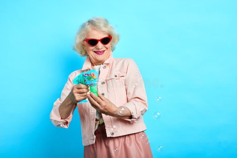 做肥皂泡的太阳镜的滑稽的时髦的魅力老婆婆 免版税库存照片