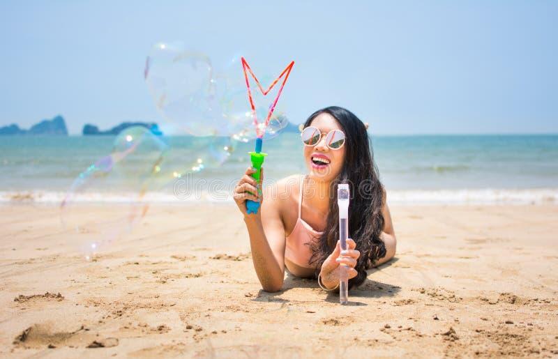 做肥皂泡的女孩在海滩 免版税图库摄影