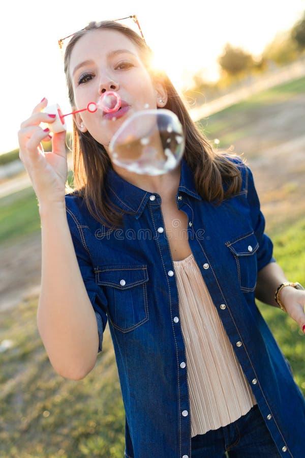 做肥皂泡的美丽的少妇在公园 免版税库存照片