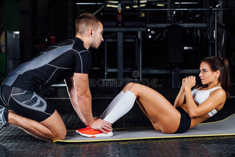 做胃肠咬嚼的妇女按在席子的锻炼有她的体育男性教练员的 库存照片