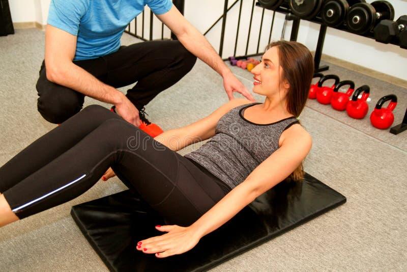 做胃锻炼的运动的人民在健身房俱乐部 免版税库存照片