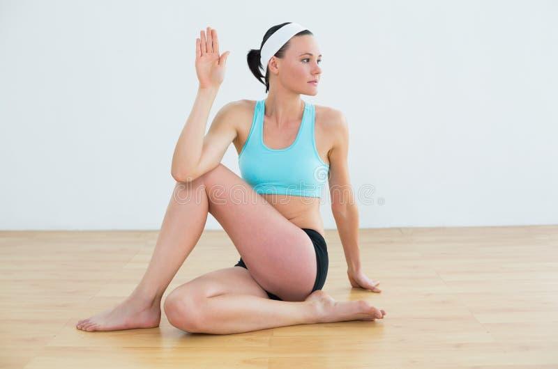 做脊椎的妇女扭转姿势在健身演播室 库存照片