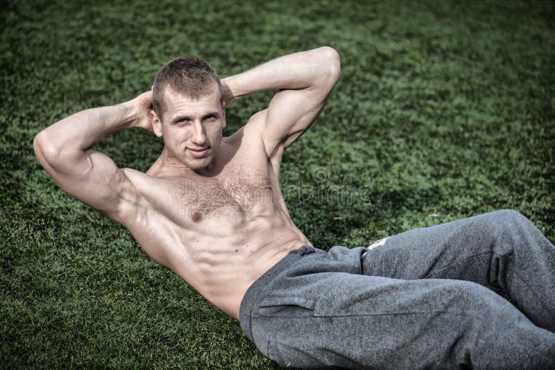 做腹肌的年轻人锻炼在绿草 免版税库存照片