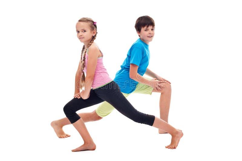 做腿加强和灵活性锻炼的孩子 免版税库存图片