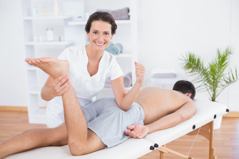 做腿按摩和微笑对照相机的生理治疗师 库存图片