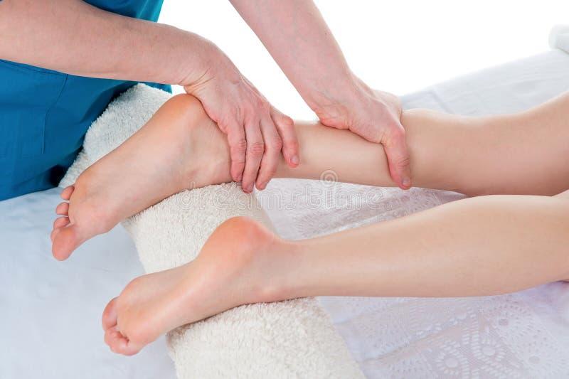 做腿按摩的生理治疗师在医疗办公室 库存照片