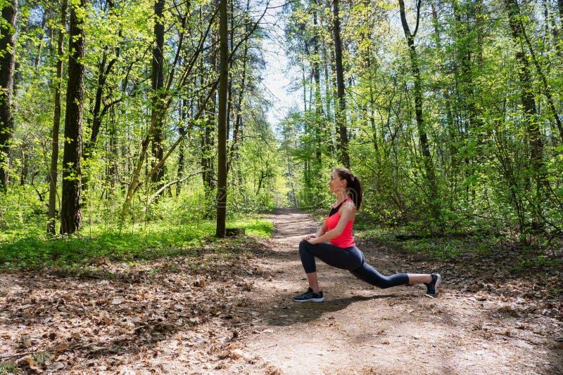 做腿的健身妇女舒展在夏天森林里 库存照片
