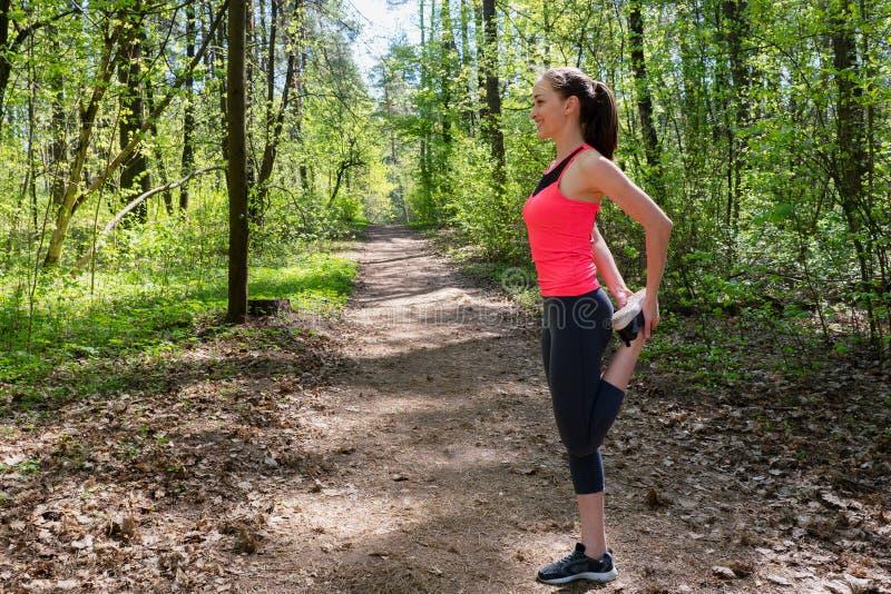 做腿的健身妇女舒展在奔跑前在森林里 免版税库存照片