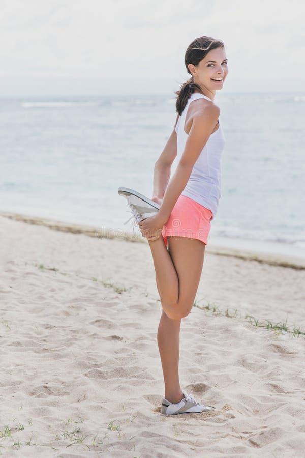 做腿的愉快的运动的妇女舒展在跑步前 免版税库存图片