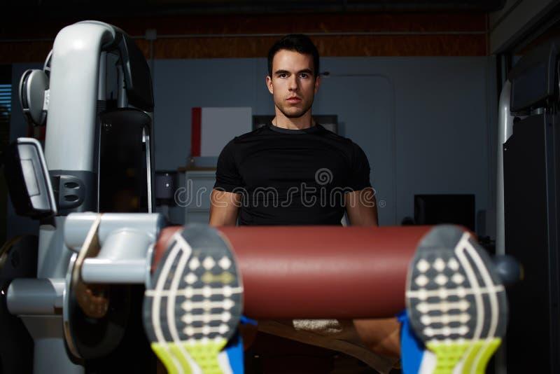 做腿的英俊的年轻运动员按在健身房 库存照片