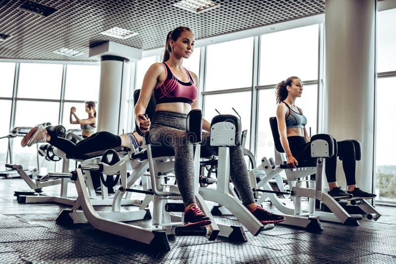 做腿稀释的坚强的女孩运动员在模拟器行使 免版税库存图片