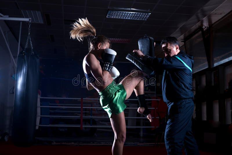 做膝盖反撞力的拳击女孩 免版税库存图片