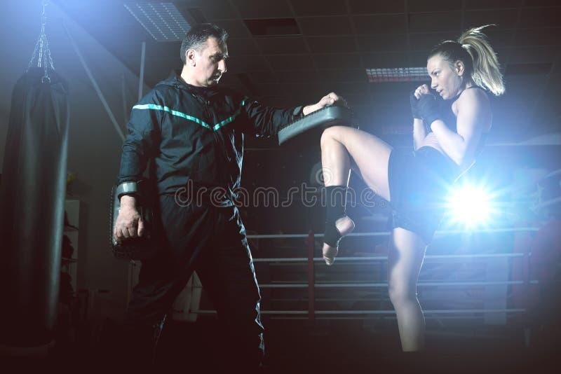 做膝盖反撞力的拳击女孩 免版税库存照片