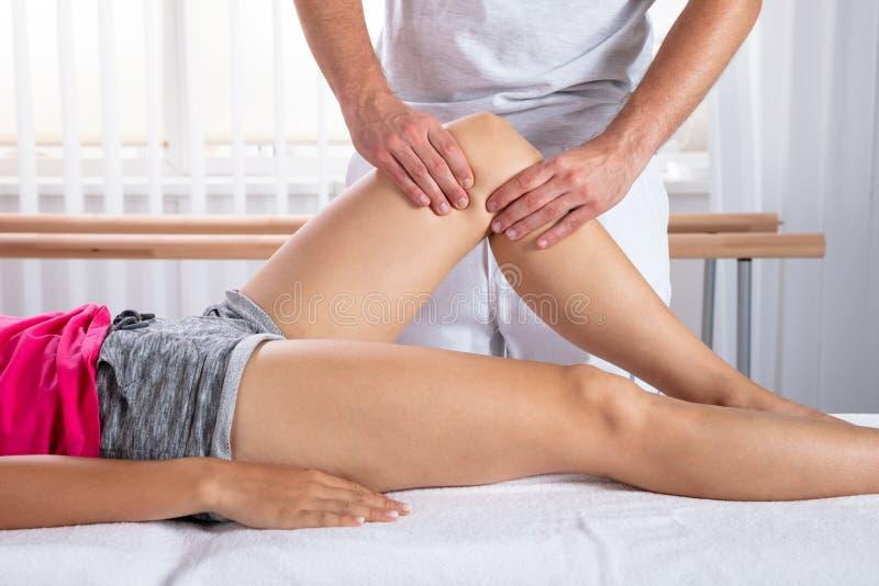 做膝盖按摩的治疗师 图库摄影