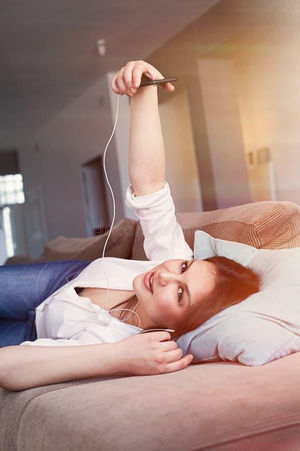 做自已图象的白色衬衫的快乐的深色的年轻女人说谎在沙发在客厅 ?? 免版税图库摄影
