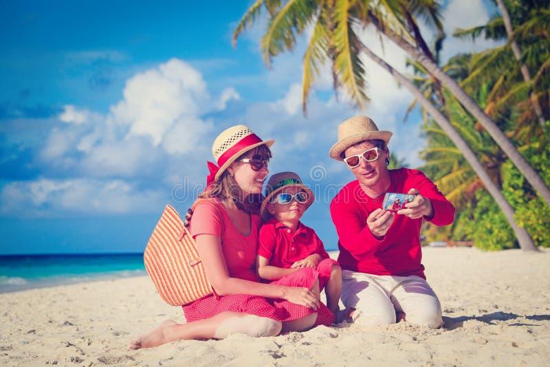 做自已照片的家庭在海滩使用电话 免版税库存图片