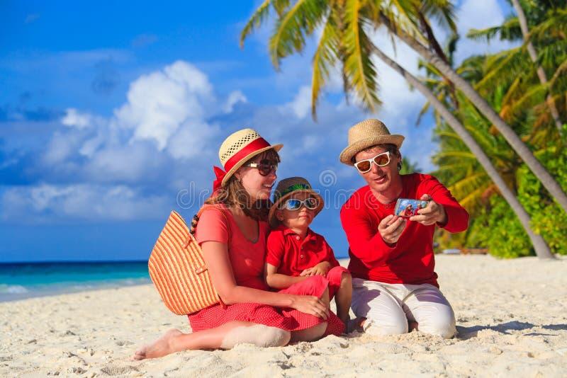 做自已照片的家庭在海滩使用电话 库存照片