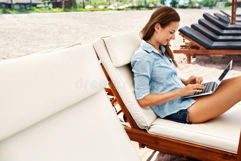 做自由职业者工作 使用在海滩的女商人计算机 网上工作 库存图片