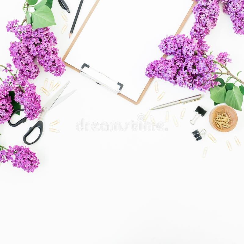 做自由职业者或与剪贴板、笔记本、剪刀、淡紫色花和辅助部件的博客作者工作区在白色背景 平的位置, 图库摄影