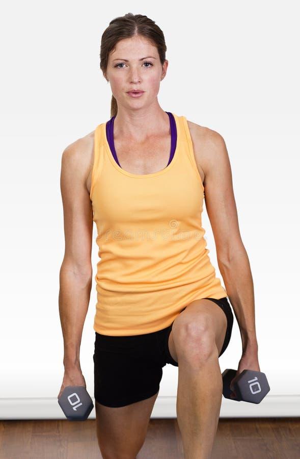 做自由重量训练的美丽,适合的妇女 免版税库存照片