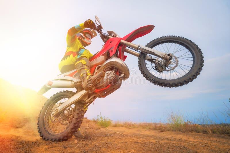做自行车前轮离地平衡特技的摩托车越野赛车手 免版税库存照片