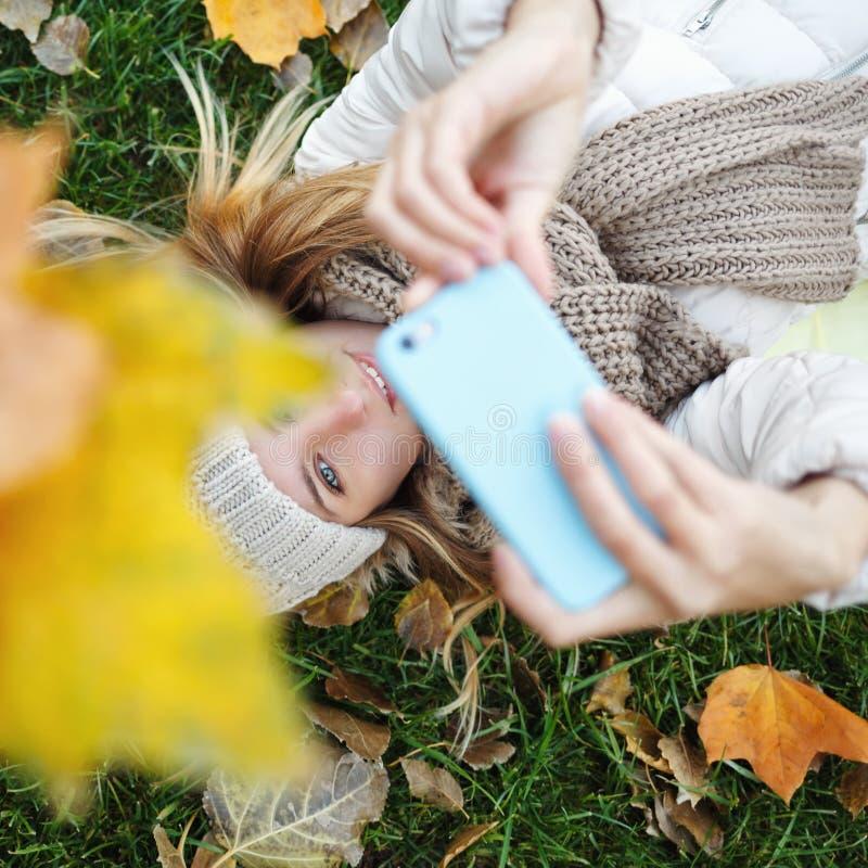 做自画象的女孩说谎在下落的叶子 秋天 免版税库存照片