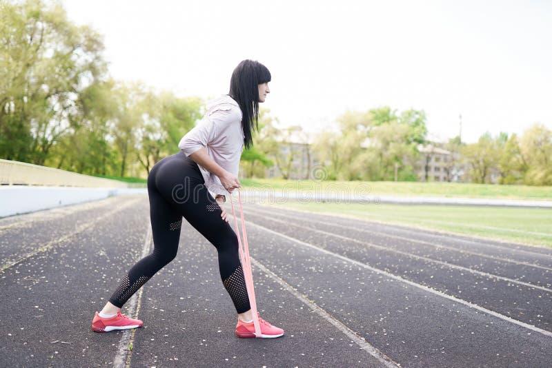 做舒展在体育场的年轻健身女孩 夏天体育活动 与拷贝空间的绿色体育场背景 库存照片