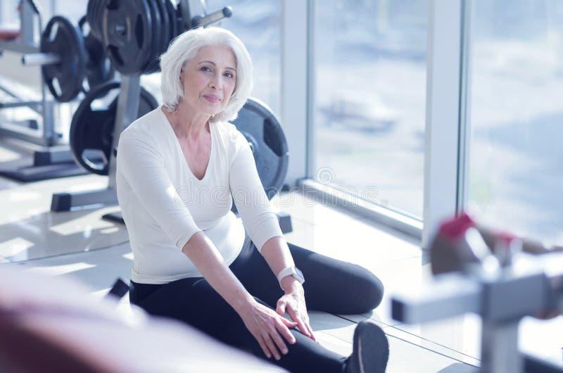 做舒展在健身房的资深夫人 免版税图库摄影