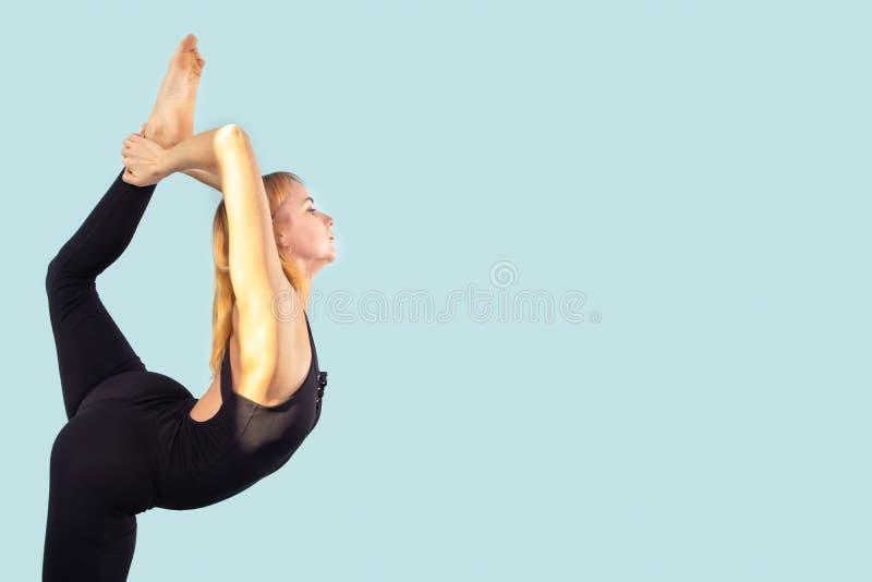 做舒展瑜伽的特写镜头可爱的年轻女人,在一间明亮的颜色屋子 免版税库存图片