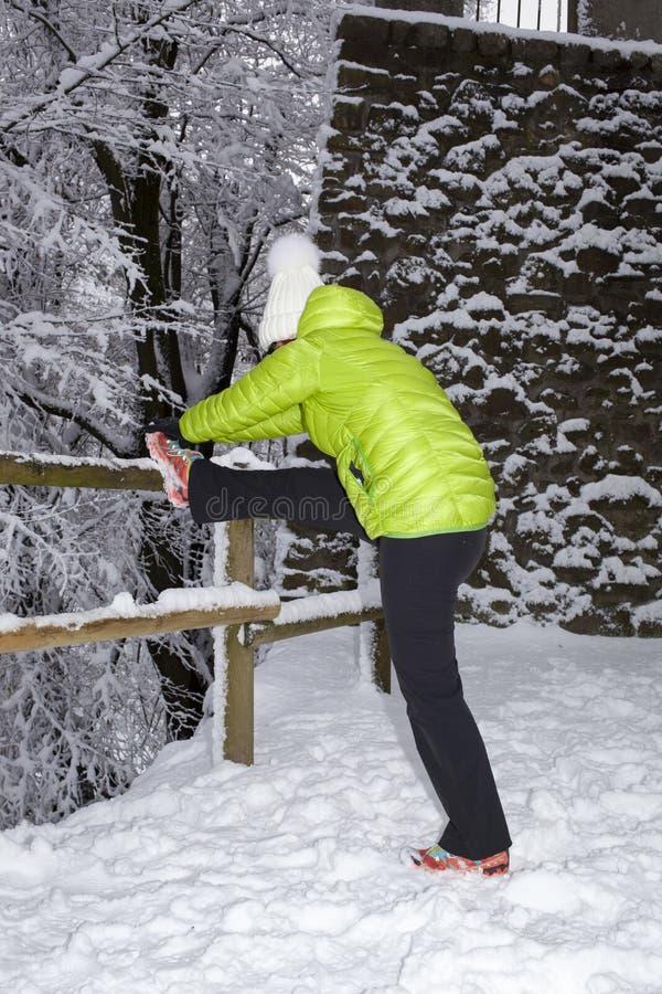 做舒展的中间年迈的妇女在冬天城市公园 库存照片