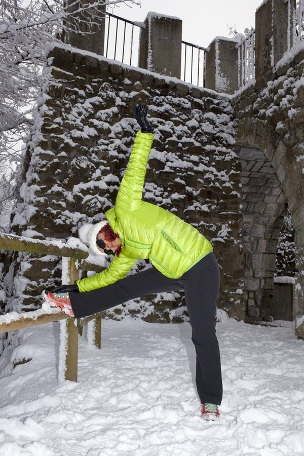 做舒展的中间年迈的妇女在冬天城市公园 免版税库存图片
