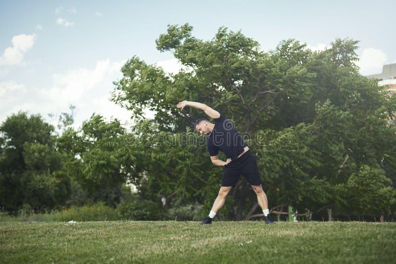 做舒展的可爱的年轻人行使用手室外在公园 免版税图库摄影