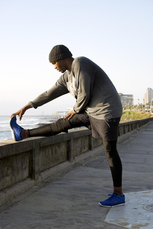 做舒展的慢跑者由路的边 免版税库存照片