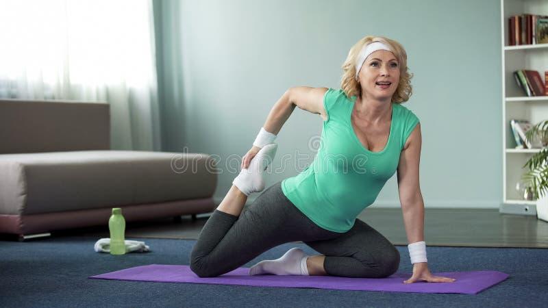 做舒展的白肤金发的中年女性在瑜伽席子在家行使,体育 免版税库存照片