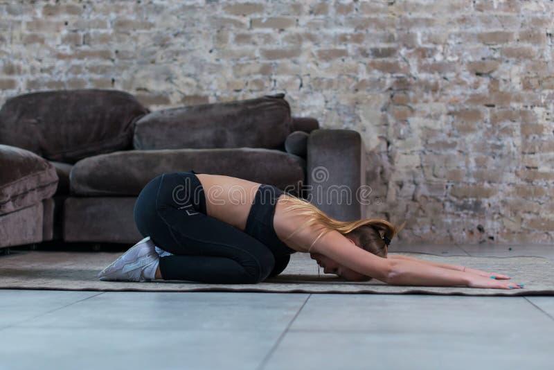 做舒展的稀薄的女孩在家站立在地板实践的瑜伽的祷告姿势的锻炼 免版税库存照片