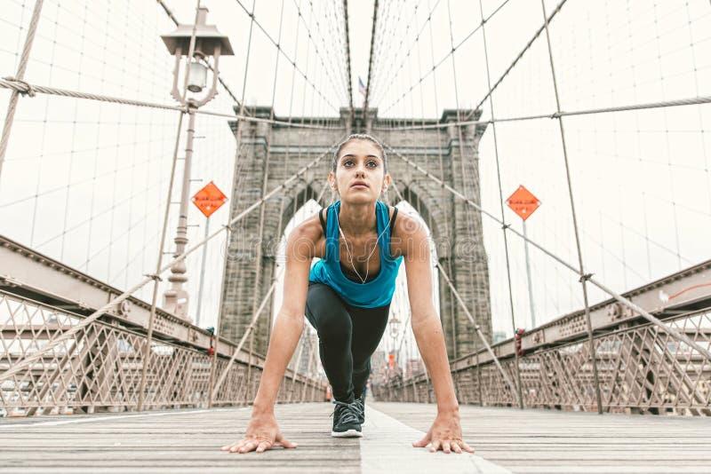 做舒展的美丽的女孩清早在跑前 布鲁克林大桥和纽约地平线在背景中 库存图片