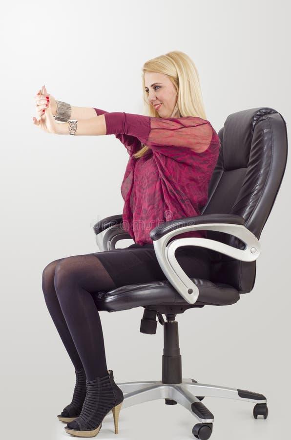 做舒展的年轻白肤金发的女实业家,当坐在椅子时 免版税库存图片