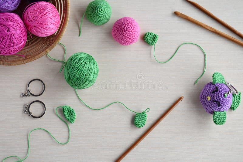 做色的钩针编织鸟 婴孩或小装饰品的玩具 在桌螺纹,针,勾子,棉纱品 手工制造礼物 DIY 免版税库存照片