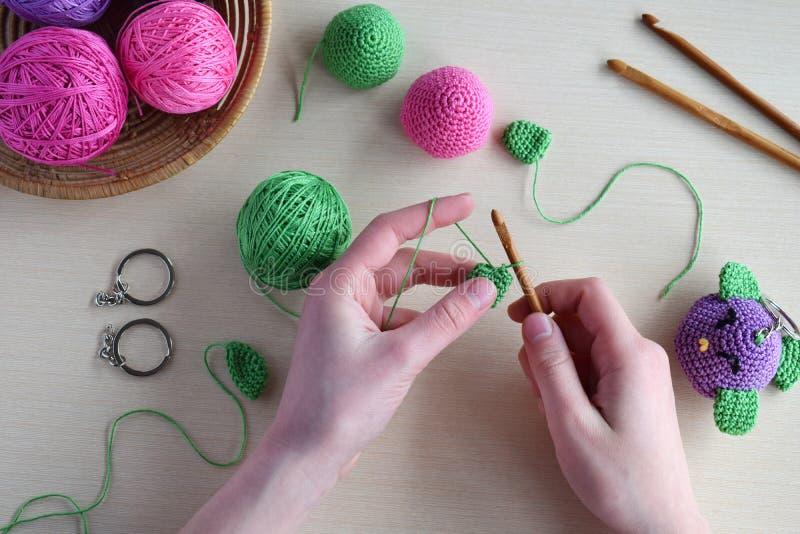做色的钩针编织鸟 婴孩或小装饰品的玩具 在桌螺纹,针,勾子,棉纱品 手工制造礼物 DIY 库存图片